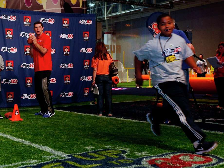 Quarterback and Quaker spokesperson Andrew Luck runs football drills with New Orleans kids at Ernest N. Morial Convention Center at Kid's Day at NFL Experience Driven by GMC in New Orleans Wednesday, Jan. 30, 2013.  Luck serves as healthy living role model and encourages kids to eat right and stay active. Photo: Jonathan Bachman, Associated Press / AP Images