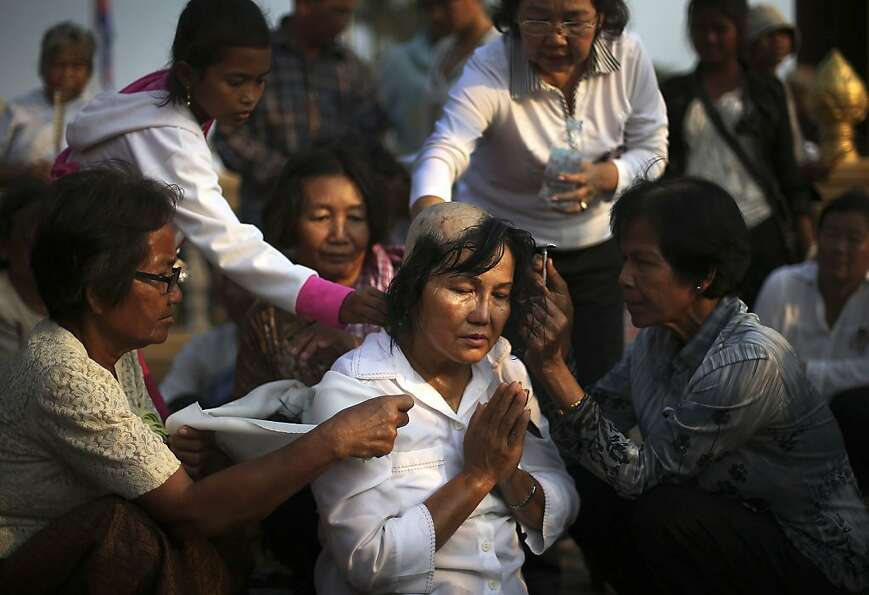 A mourner prays as her head is shaved out of respect for the late Cambodian King Norodom Siha