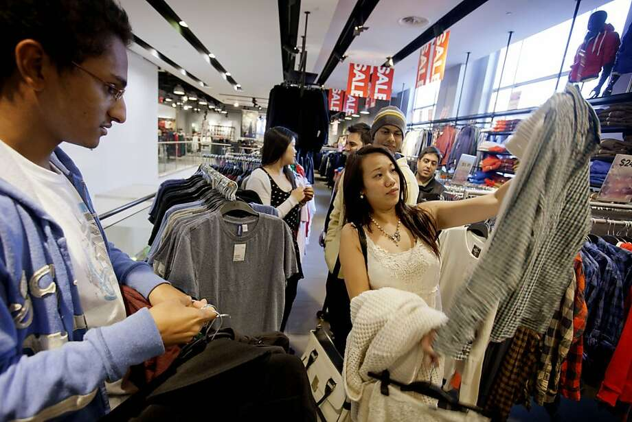 In an Atlanta H&M store, Lana Nguyen (right) shows friend Chris Ghiathi an item. H&M is struggling with a sales slowdown and other challenges. Photo: David Goldman, Associated Press