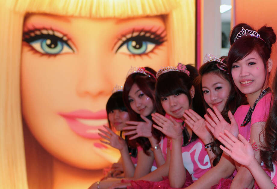 Waitresses wave in front of a Barbie poster. Photo: SAM YEH, AFP/Getty Images / 2013 AFP