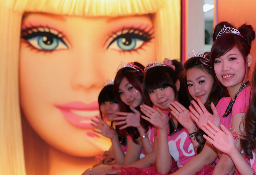 Waitresses wave in front of a Barbie poster.
