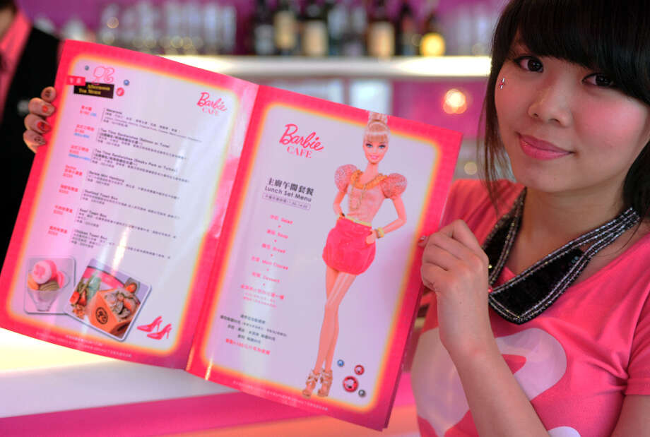 A waitress holds up a menu at the Barbie Cafe. Photo: SAM YEH, AFP/Getty Images / 2013 AFP
