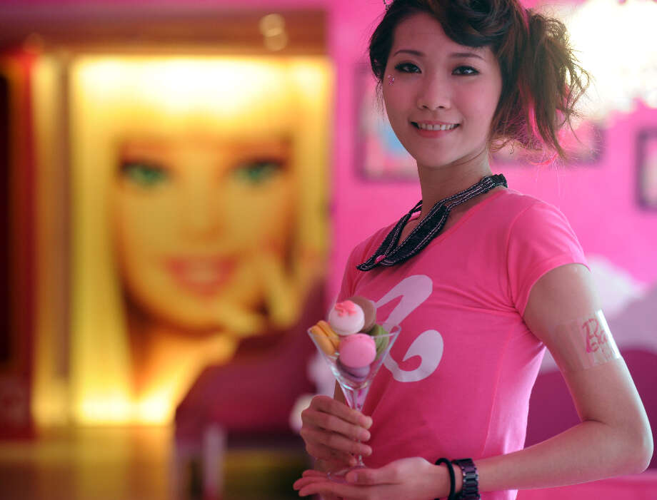 A waitresses poses as she displays a cup of macaroons. Photo: SAM YEH, AFP/Getty Images / 2013 AFP