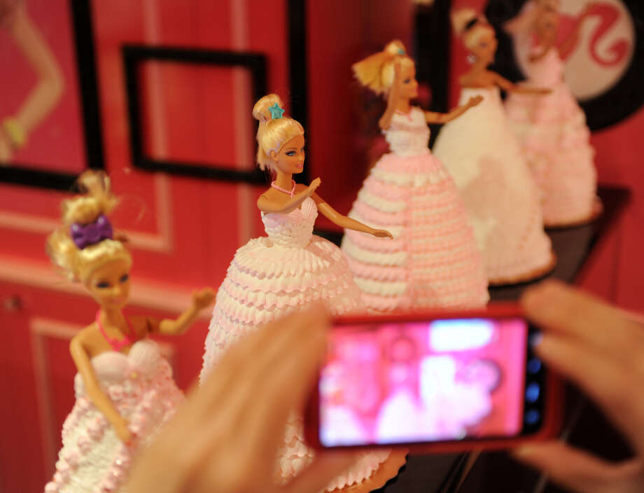A Barbie fan takes pictures of the cakes. Photo: SAM YEH, AFP/Getty Images / 2013 AFP