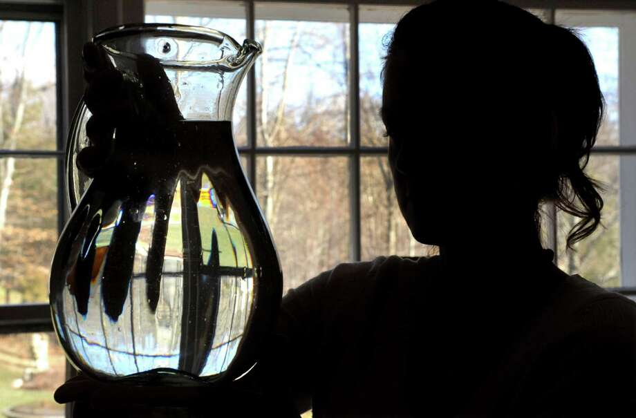 Jessica Penna holds a pitcher of water in her Weston home on Thursday, January 31, 2013. Penna's home has well-water which is contaminated with arsenic and Penna believes the arsenic has caused her health problems. Photo: Lindsay Perry / Stamford Advocate
