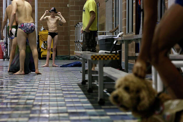 Churchill swimmer Ben Ownby, left, gets ready for practice with the Alamo Area Aquatics club team while his service dog, Dakota, right, sits patiently, right, and gets a rub on his head from another swimmer at Josh Davis Natatorium in San Antonio on Tuesday, Jan. 29, 2013. Photo: Lisa Krantz, Express-News / © 2012 San Antonio Express-News