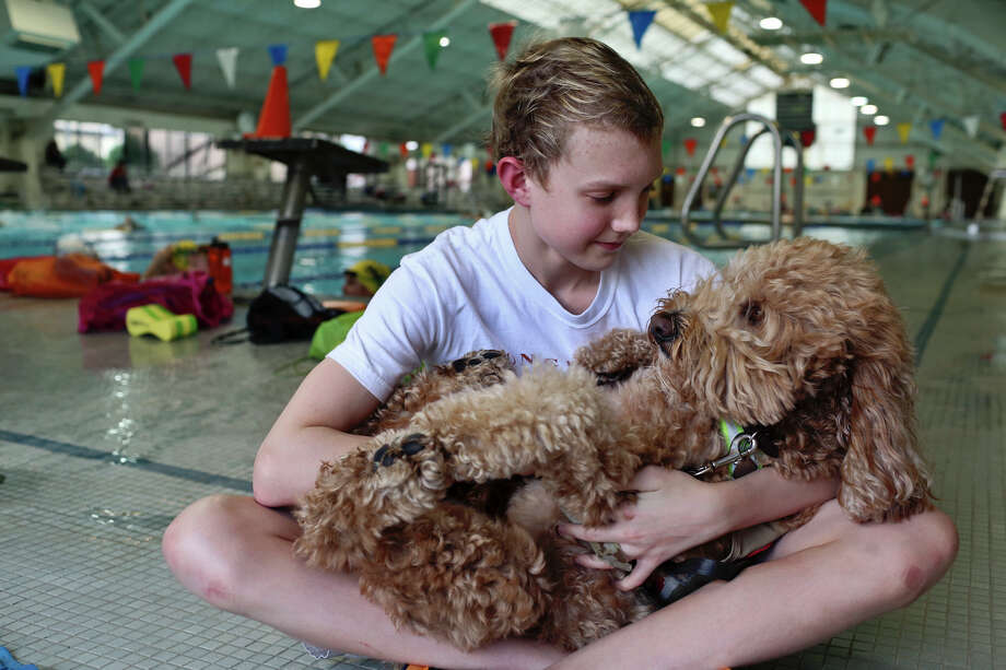 Churchill swimmer Ben Ownby holds his service dog, Dakota, before  practice with the Alamo Area Aquatics club team at Josh Davis Natatorium in San Antonio on Tuesday, Jan. 29, 2013. Photo: Lisa Krantz, Express-News / © 2012 San Antonio Express-News