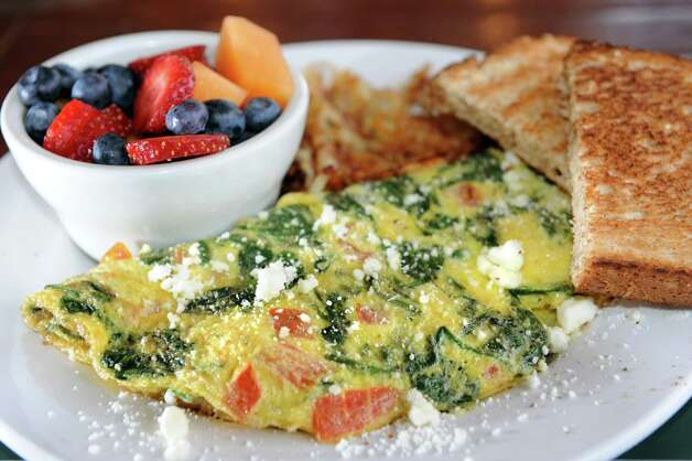 Mediterranean omelet with roasted tomatoes, spinach and feta cheese on ...