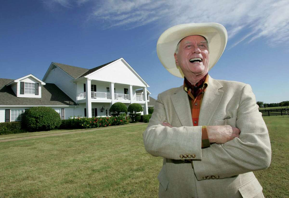 FILE - In this Oct. 9, 2008, file photo, the late Actor Larry Hagman poses in front of the Southfork Ranch mansion made famous in the television show,
