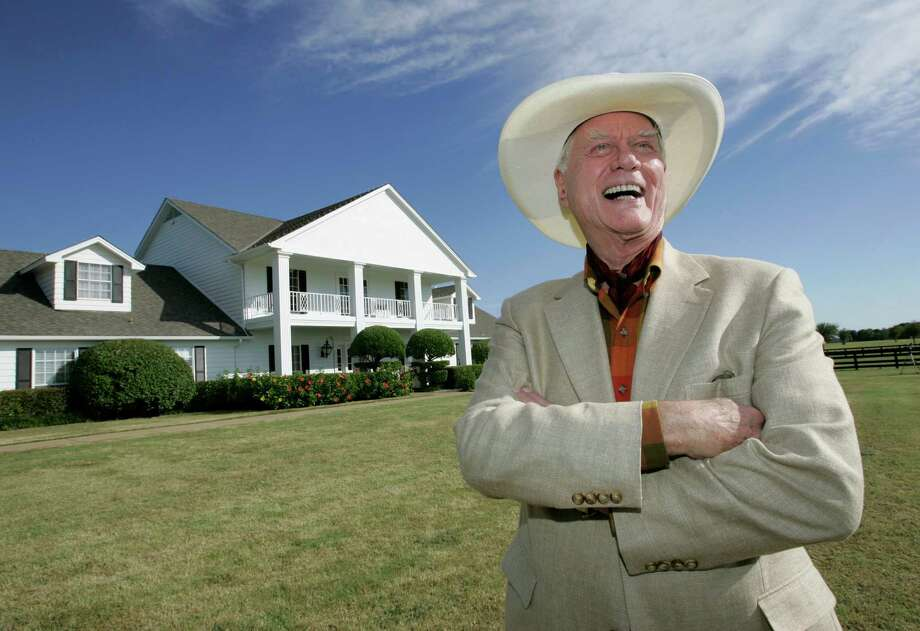 "FILE - In this Oct. 9, 2008, file photo, the late Actor Larry Hagman poses in front of the  Southfork Ranch mansion made famous in the television show, ""Dallas"",  in Parker, Texas. Tourists have been flocking to Southfork Ranch since the early years of the classic series, which ran from 1978 to 1991. And a new ""Dallas"" starting its second season on TNT on Monday and the recent death of the show's star, Larry Hagman, who legendarily played conniving Texas oilman J.R. Ewing, have also spurred fans to visit. (AP Photo/Tony Gutierrez, file) Photo: Tony Gutierrez"