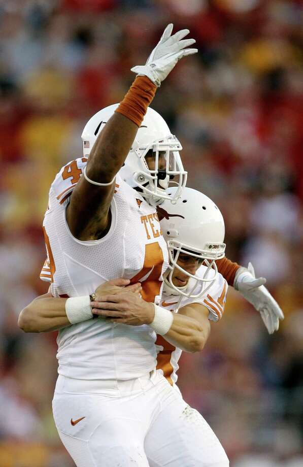 Texas linebacker Tevin Jackson, left, celebrates with teammate Justin Tucker after recovering a fumble during the first half an NCAA college football game against Iowa State, Saturday, Oct. 1, 2011, in Ames, Iowa. Texas won 37-14. (AP Photo/Charlie Neibergall) Photo: Charlie Neibergall, Associated Press / AP