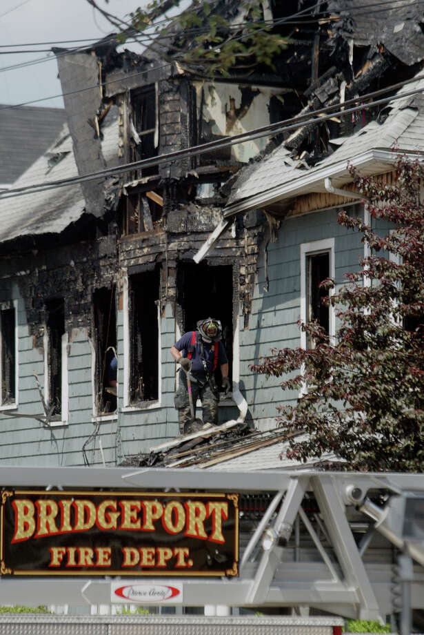 June 13th, 2005 - A Bridgeport firefighter cleans at 1647-1649 Iranistan Ave., where Thi Luong, 35, her son Hoang Anh, 14, daughter Thi My Trinh, 11, and 3-year-old daughter Daisy were killed when unable to escape the 4 a.m. fire that engulfed the three-story, multi-family home. Rinh Thach survived the fire. Photo: File Photo/Phil Noel, File Photo / Connecticut Post File Photo