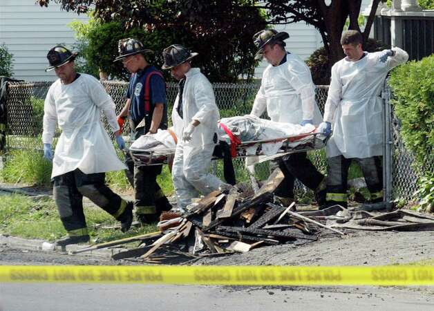 June 13th, 2005 - Bridgeport firefighters remove a body from 1647-1649 Iranistan Ave., where Thi Luong, 35, her son Hoang Anh, 14, daughter Thi My Trinh, 11, and 3-year-old daughter Daisy were killed when unable to escape the 4 a.m. fire that engulfed the three-story, multi-family home. Rinh Thach survived the fire. Photo: Phil Noel