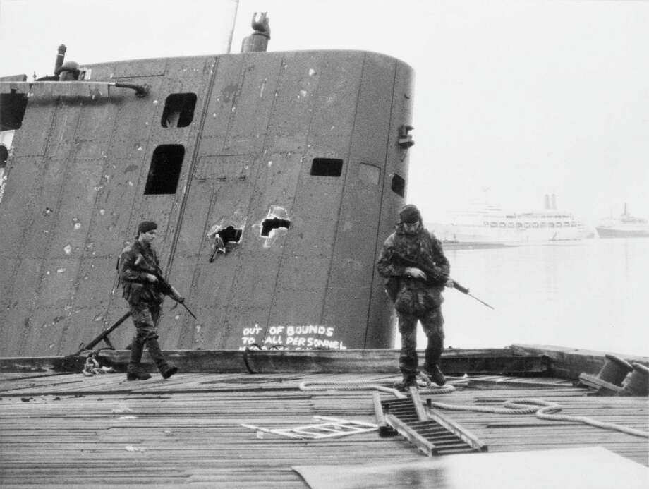 British Royal Marines patrol past the damaged fin of the abandoned Argentine submarine Sante Fe following the recapture of South Georgia in the Falkland Islands, in June 1982. Photo: IWM/Getty Images, Crown Copyright. IWM Via Getty Images / Crown copyright. IWM (FKD 978)