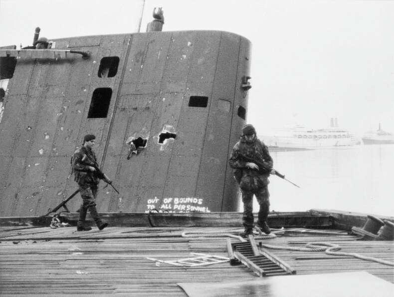British Royal Marines patrol past the damaged fin of the abandoned Argentine submarine Sante Fe foll