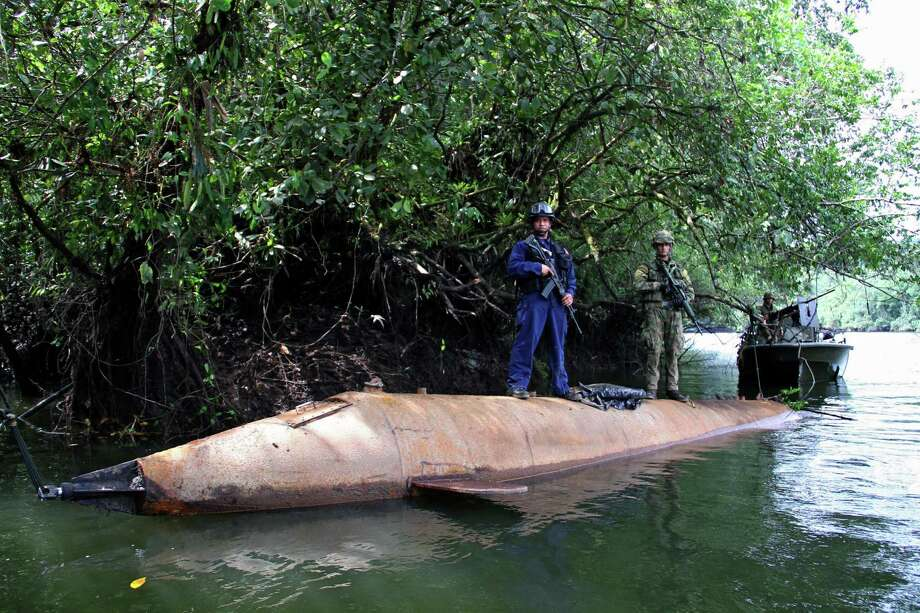 Colombian soldiers guard a homemade submersible in a forest area of the Cajambre river near Buenaventura, Colombia, on May 29, 2012.  The Colombian Navy seized the sub, which could transport up to five tons of drugs. Photo: AFP, AFP/Getty Images / 2012 AFP