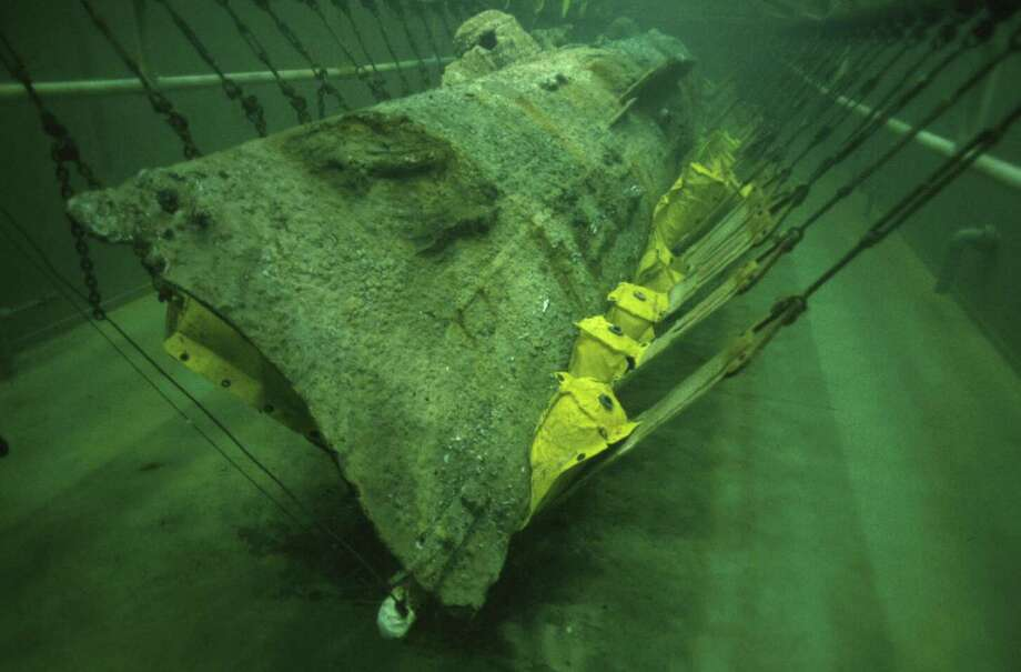 Here, the Hunley sits in a preservation tank. For years, historians had speculated the crew ran out of air before they were able to return to shore. Inside the sub, the crew members were found at their seats, with no evidence of an attempt to abandon ship. Photo: Getty Images / 2004 Getty Images