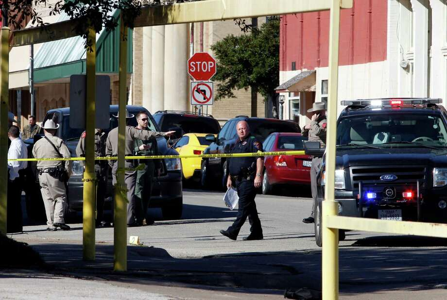 Law enforcement officers investigate at the scene of a shooting in downtown Kaufman, Texas on Thursday morning, January 31, 2013. The Kaufman County sheriff has identified the assistant DA shot and killed by masked gunmen this morning as Mark Hasse, a onetime Dallas County prosecutor. (David Woo/Dallas Morning News/MCT) Photo: David Woo, McClatchy-Tribune News Service / Dallas Morning News