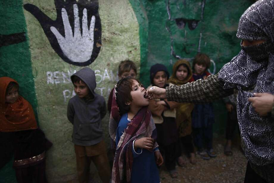 A girl whose family was displaced from their home by fighting in tribal areas receives polio vaccine. Eleven health care workers providing the vaccine have been killed in recent months. Photo: Muhammed Muheisen, Associated Press