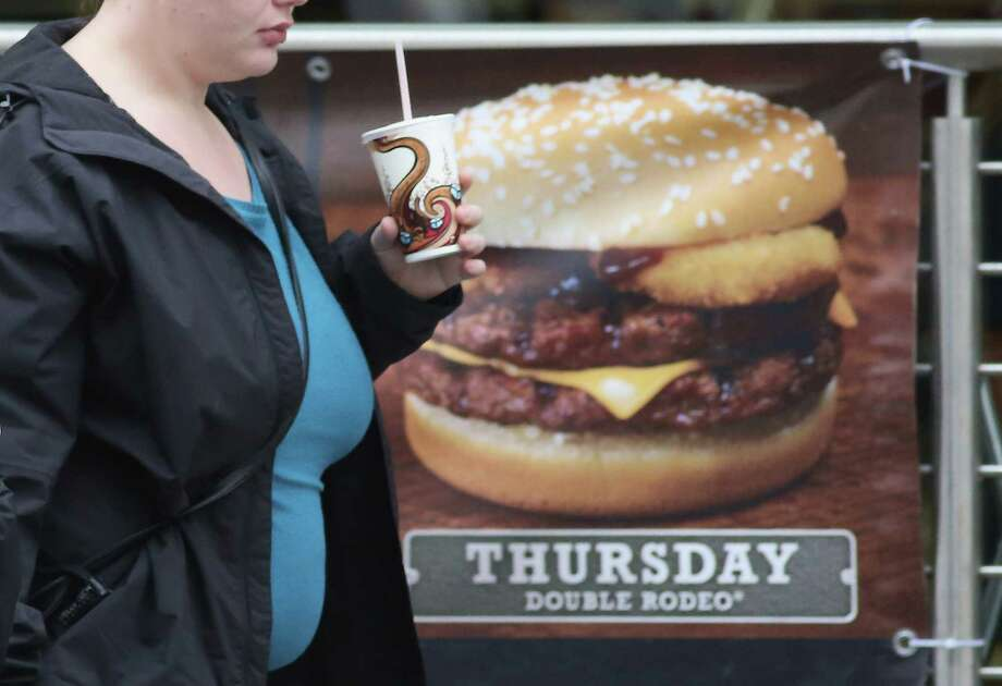 BRISTOL, ENGLAND - JANUARY 07:  A woman passes an advertisement outside a fast food outlet on January 7, 2013 in Bristol, England.  A government-backed TV advert - made by Aardman, the creators of Wallace and Gromit - to promote healthy eating in England, is to be shown for the first time later today. England has one of the highest rates of obesity in Europe - costing the NHS 5 billion GDP each year - with currently over 60 percent of adults and a third of 10 and 11 year olds thought to be overweight or obese. Photo: Matt Cardy, Getty Images / 2013 Getty Images