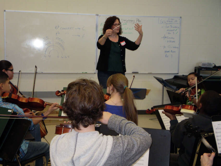 Thanks to a grant from the Fairfield County Community Foundation, 29 Bridgeport string students are learning how to perform in an orchestra setting with the help of the Greater Bridgeport Youth Orchestras. Above, Erica Messina, a GBYO conductor, works with the group in Fairfield. Photo: Contributed Photo