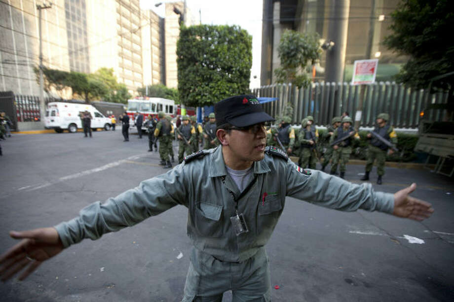 A worker belonging to Mexico's state-owned oil company PEMEX keeps journalists away after an explosion at an adjacent building to the executive tower of PEMEX in Mexico City, Thursday Jan. 31, 2013. An explosion at the main headquarters of Mexico's state-owned oil company in the capital Thursday left at least several workers injured, blew out windows and damaged the building, the company said.