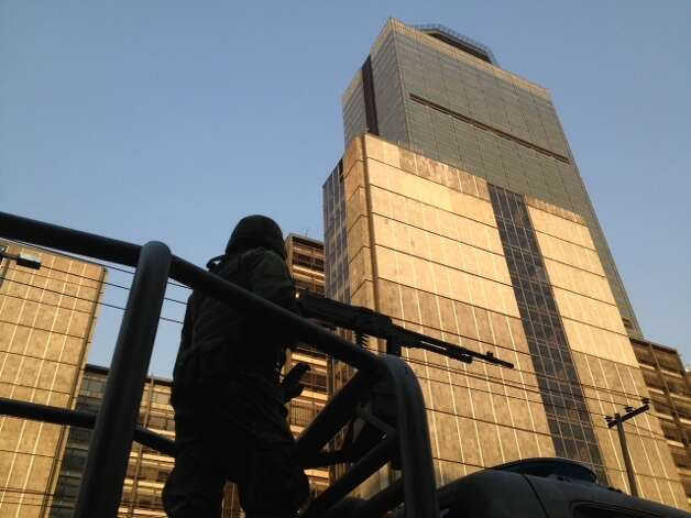A soldier stands guard outside the Pemex headquarters after an explosion in Mexico City, Thursday, Jan. 31, 2013. Mexico's state-owned oil company says an explosion at its headquarters in the capital has left several workers injured. Photo: Eduardo Verdugo