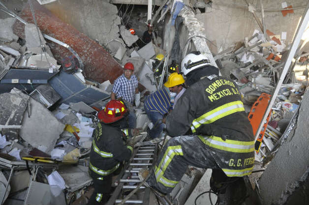 Firefighters belonging to the Tacubaya sector and workers dig for survivors after an explosion at an adjacent building to the executive tower of Mexico's state-owned oil company PEMEX, in Mexico City, Thursday Jan. 31, 2013.