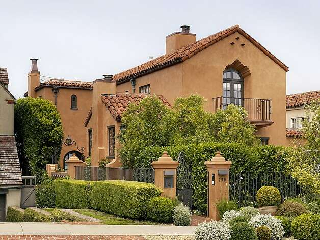 This Sea Cliff property, selling for $6.5 million, shows Spanish influence in its red tiled roof, terra cotta facade, wrought-iron work and lantern lighting. Photo: Malin Giddings