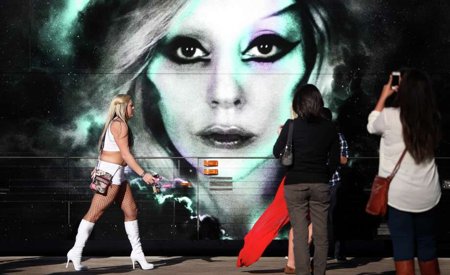 Fans photograph a painting of Lady Gaga in front of the Born This Way Ball Tour bus outside Toyota Center on Thursday, Jan. 31, 2013, in Houston.Read our review of Gaga's show here.  Photo: Mayra Beltran, Houston Chronicle / © 2013 Houston Chronicle