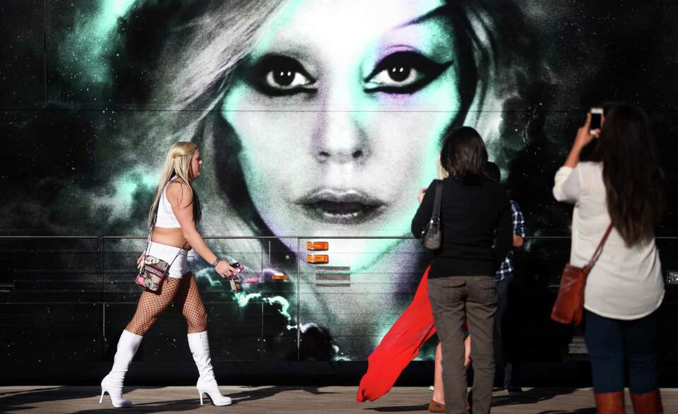 Fans photograph a painting of Lady Gaga in front of the Born This Way Ball Tour bus outside Toyota C
