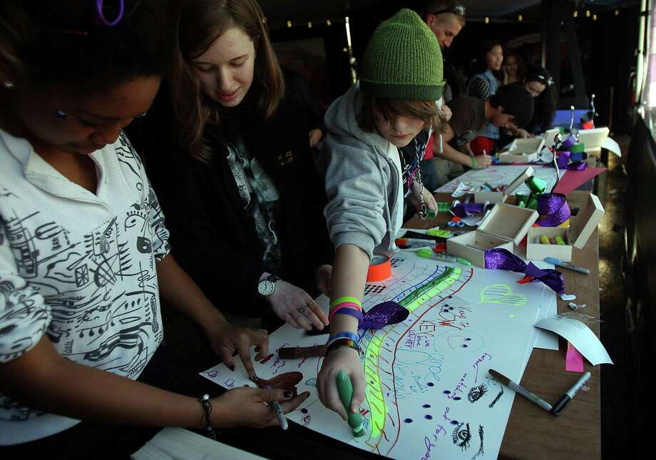 Micaela Williams, Sarah Lach, and Aidan Maples draw a poster for the concert during the event around the Born Brave Bus before the Lady Gaga Concert at the Toyota Center on Thursday, Jan. 31, 2013, in Houston. The Born This Way Foundation tries to inspire bravery and promote self-acceptance. Photo: Mayra Beltran, Houston Chronicle / © 2013 Houston Chronicle
