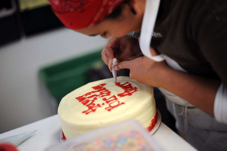 Baker Denise Maladonado of Oakland, ices a Happy Birthday inscription onto a cake for a customer.  Susie Cakes Bakery on Chestnut St. has already received 400 orders for specialty 49er cakes, cupcakes and cookies, in San Francisco, CA on Wednesday January 30th, 2013.
