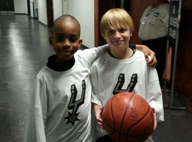 Nolan Teich (right) holds the autographed Spurs basketball he received Saturday as a reward for donating his ball in October to Jonathan Lankford Jr. (left) whose father was killed while serving in Iraq in 2007. Photo: COURTESY / COURTESY OF THE LANKFORD FAMILY