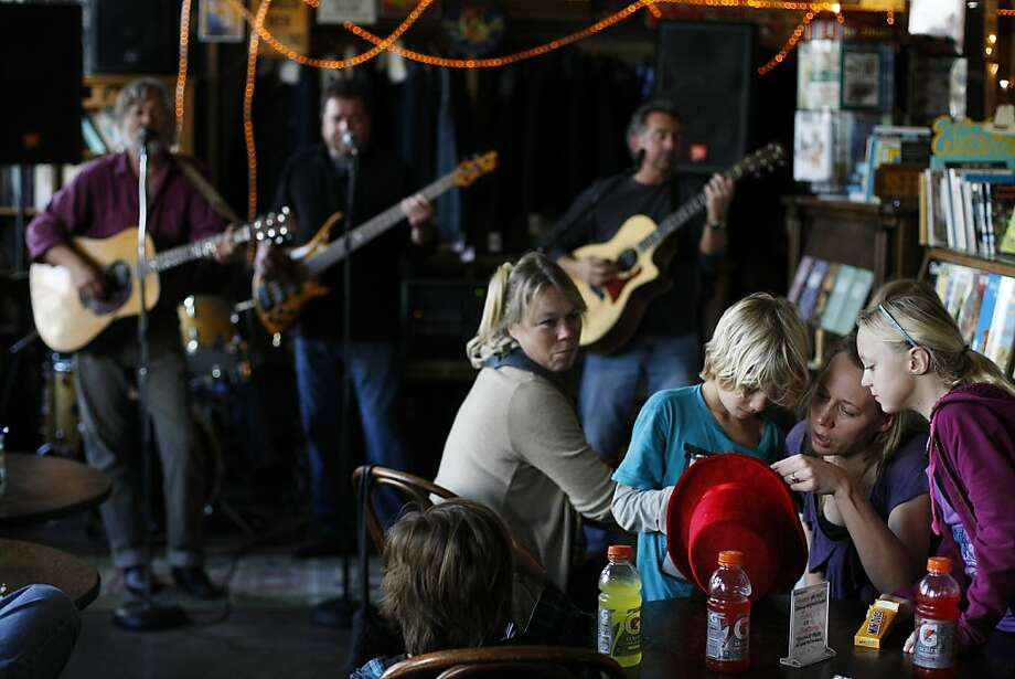 Annemieke Dodd (second from right) checks out a hat with Ozan Soult (second from left) and Tallulah Alexander (right) as a band plays at the general store. Photo: James Tensuan