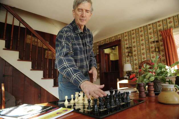 Richard Moody Jr., moves chess pieces on a board as he talks about how he plays the game at his home on Thursday, Jan. 24, 2013 in Wright, NY.  Moody says that he has a method for playing against a computer and bringing the game to a draw.    (Paul Buckowski / Times Union) Photo: Paul Buckowski  / 00020876A