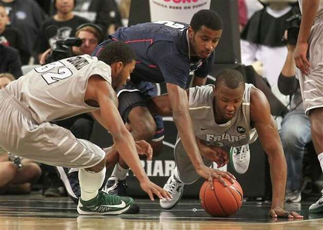 Providence guard Vincent Council (32) forward Kadeem Batts, right, and Connecticut forward DeAndre Daniels (2) battle for the loose ball during the first half of an NCAA college basketball game, Thursday, Jan. 31, 2013, in Providence, R.I. (AP Photo/Stew Milne)