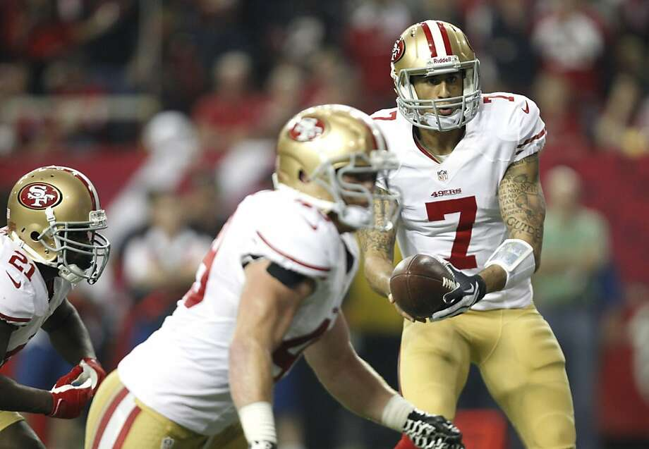 On read-option plays with the 49ers, Kaepernick decides whether to hand the ball to the tailback, Frank Gore (No. 21) in this case, or keep it and begin running around the end. Photo: Michael Macor, The Chronicle