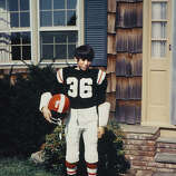Steve Young as a 10-year-old  member of the Cowboys football team, standing in front of his parent's house in  Greenwich.