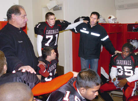 During a return to his alma mater in October 2006, Steve Young, second from right, takes part in a team prayer in the Greenwich High School locker room just prior to the start of the GHS vs. Norwalk Homecoming game in October 2005.  Also in photo are, GHS head footaball coach, Rich Albonizio, left, Jon Seraphin, #71,  Chris Flores, #35, right and Mik Boodoosingh, #19 , bottom. Photo: Bob Luckey Jr., GT