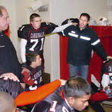 During a return to his alma mater in October 2006, Steve Young, second from right, takes part in a team prayer in the Greenwich High School locker room just prior to the start of the GHS vs. Norwalk Homecoming game in October 2005.  Also in photo are, GHS head footaball coach, Rich Albonizio, left, Jon Seraphin, #71,  Chris Flores, #35, right and Mik Boodoosingh, #19 , bottom.