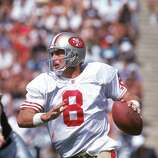 Quarterback Steve Young #8 of the San Francisco 49ers looks to pass against the Los Angeles Raiders during a game at the Los Angeles Memorial Coliseum on September 29, 1991 in Los Angeles, California.  The Raiders won 12-6.  (Photo by George Rose/Getty Images)