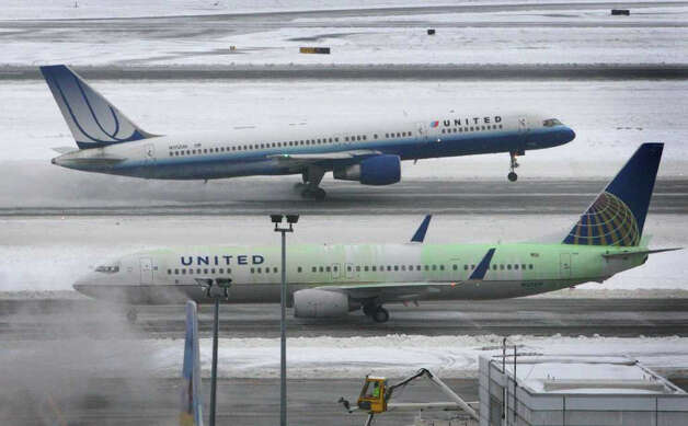 An airplane lands as another, just treated with green-tinted de-icer, begins to taxi at Seattle-Tacoma International Airport on Thursday, January 19, 2012. Crews used de-icer, plows and brooms to keep the airport operating after an early morning closure. Photo: JOSHUA TRUJILLO / SEATTLEPI.COM