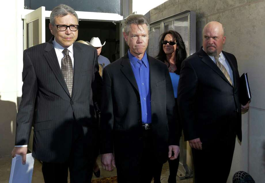 Entertainer Randy Travis, center, exits Grayson County Courthouse with his lawyer Larry Friedman, left, and an unidentified persons, right, Thursday, Jan. 31, 2013, in Sherman, Texas. Travis plead guilty to driving while intoxicated in a plea agreement with the court and will pay a $2,000 fine and serve a two year probation. (AP Photo/Tony Gutierrez) Photo: Tony Gutierrez, STF / AP