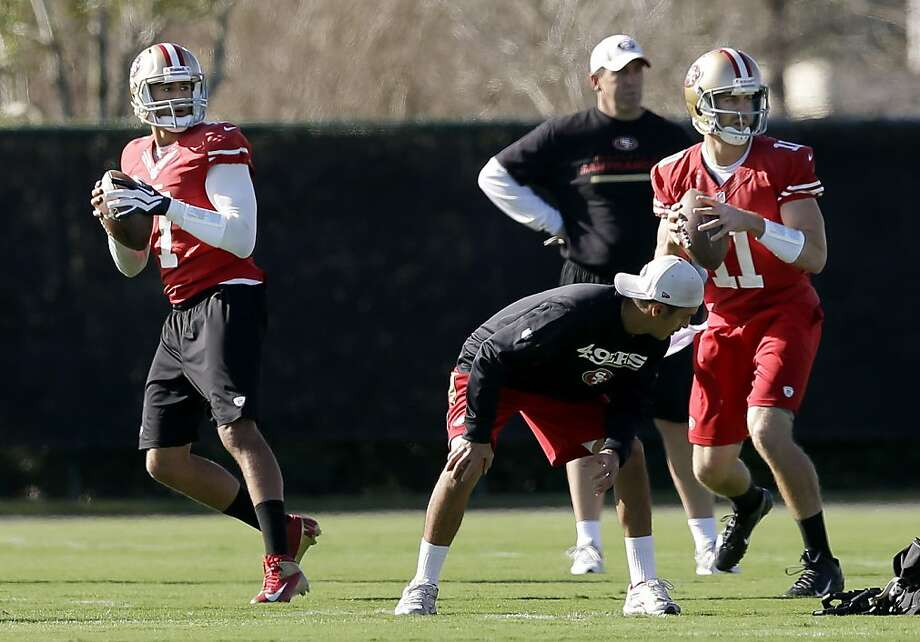"Alex Smith (right) and Colin Kaepernick drop back side by side during pre-Super Bowl practice in New Orleans. Owner Jed York says ""a lot of things"" will go into determining Smith's fate with the team. Photo: Mark Humphrey, Associated Press"