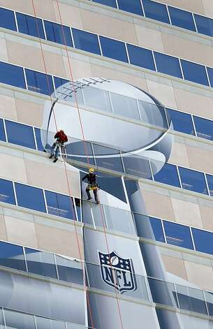 Workers repel down the face of the Benson Tower building in downtown New Orleans to cover the side of the building with the Super Bowl XLVII trophy logo for all to see Thursday January 31, 2013. Photo: Brant Ward, The Chronicle