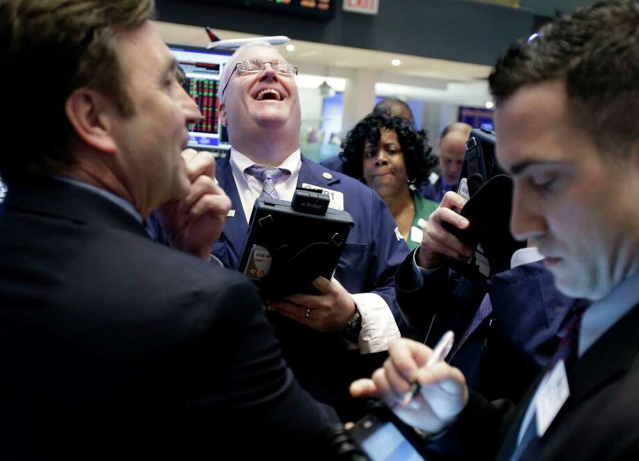 A trader laughs while working on the floor of the New York Stock Exchange in New York, Thursday, Jan. 31, 2013. The Dow edged higher Thursday, keeping the index on track for its best start to the year in more than two decades. (AP Photo/Seth Wenig)* Photo: Seth Wenig