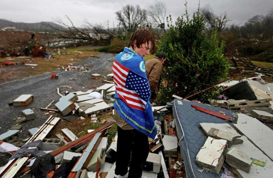 Will Carter, 15, wraps himself up in a towel he found while searching debris for the family dog, a pit bull named Niko, upon arriving to his damaged home from school following a tornado, Wednesday, Jan. 30, 2013, in Adairsville, Ga. A fierce storm system that roared across Georgia has left at least one person dead after it demolished buildings and flipped vehicles on Interstate 75 northwest of Atlanta. (AP Photo/David Goldman) Photo: David Goldman