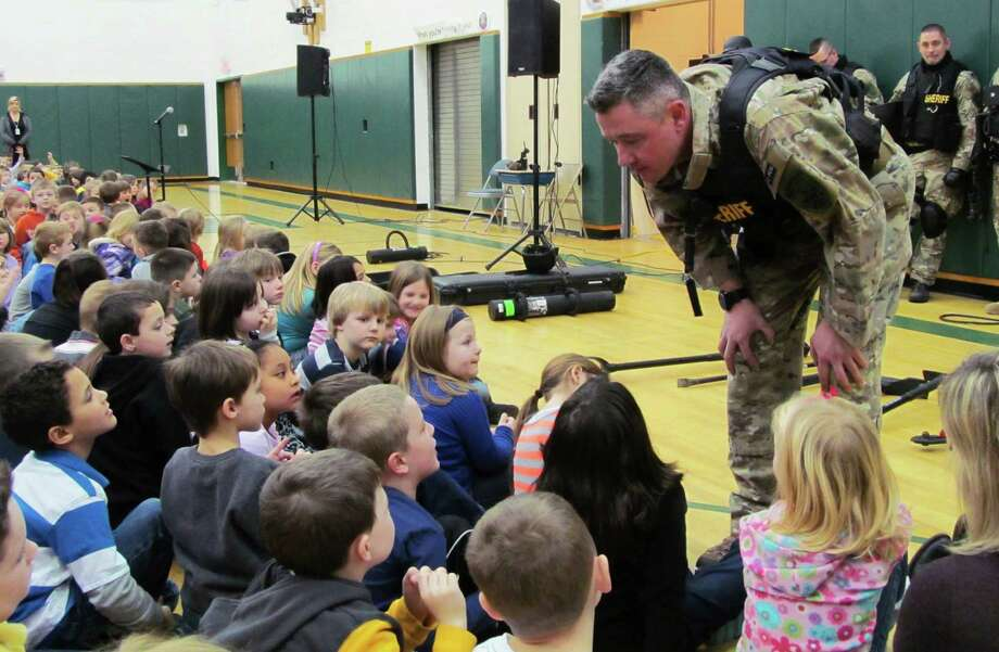 FILE - In this file photo of Jan. 28, 2013, Capt. Bryn Reynolds of the Washington County Sheriff's Office takes a question from a student at the Hudson Falls Primary School in Hudson Falls, N.Y. Reynolds and other officers were present to show off their equipment and discuss safety and to practice drills with unloaded guns to prepare for armed intruders at the school. School security has come under more scrutiny in the wake of the Sandy Hook Elementary School massacre in Newtown, Conn., that killed 26 people in December. (AP Photo/The Post-Star, Omar Ricardo Aquije, File) Photo: Omar Ricardo Aquije