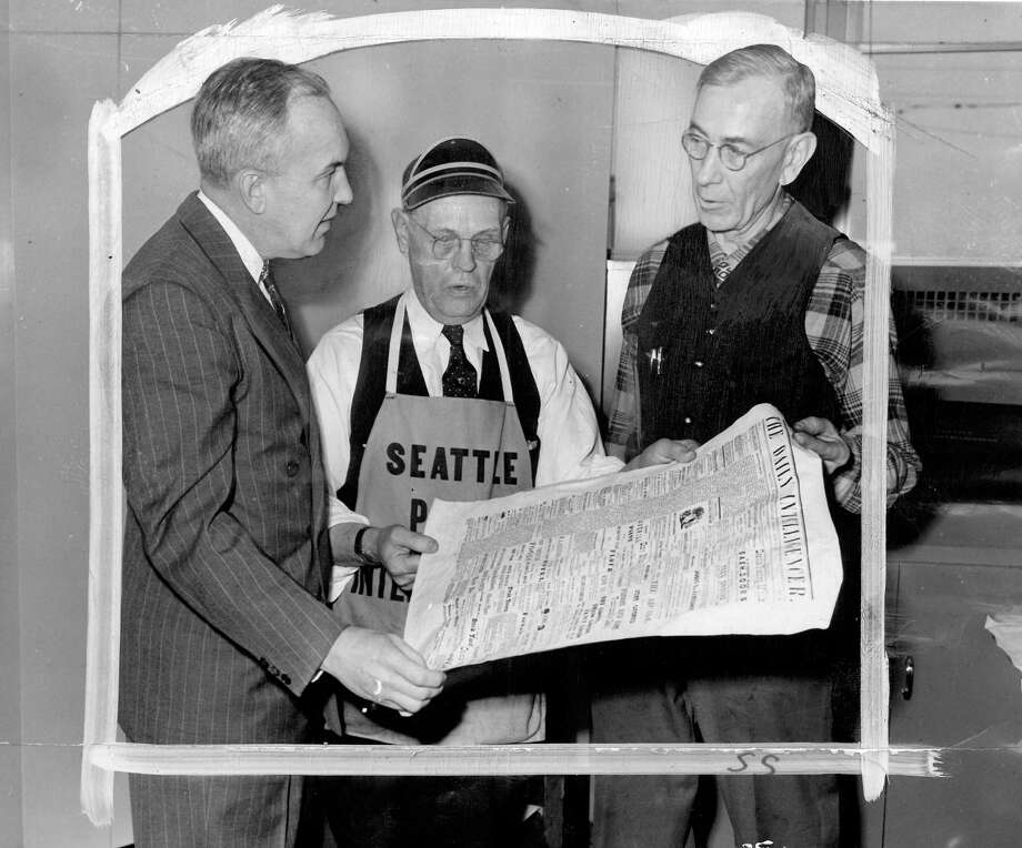 In this picture from Jan. 3, 1949 – the day the new P-I building at Sixth Avenue and Wall Street opened to the public – Mayor William F. Devin, left, Ike Ransley, P-I pressman, and Sam Hickson, P-I head machinist, post with a reproduction of the Daily Intelligencer. Marks were made by a P-I photo editor. Photo: Seattlepi.com